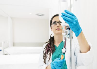 Young woman doctor anesthesiologist dressed in green gown, puts